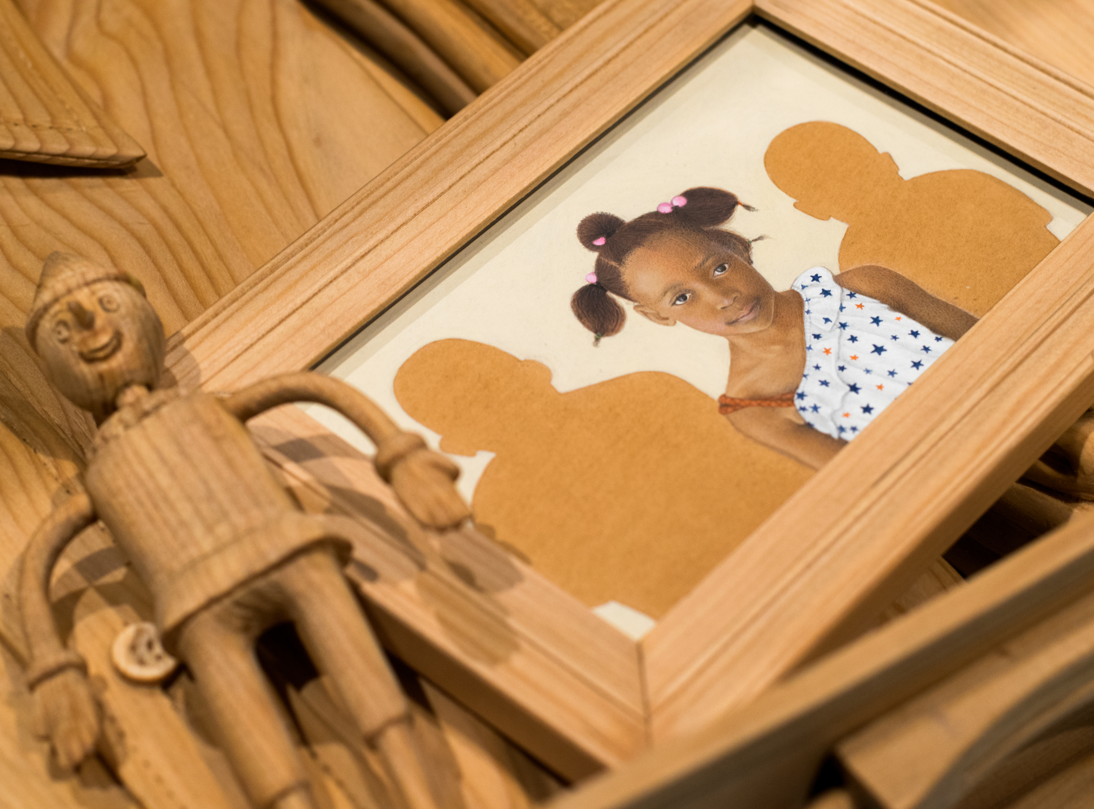 Title: Searching for Home (detail) Medium: Pine wood, carved; red wood stain.  Dimensions: Objects: dimensions vary, installation: 19 x 72 x 36 inches year: 2016-17 Photo credits: Adeel Ahmed  Portrait: Leila, Age 5 1/2, Zambia Medium: Gouache and pigments on handmade wasli paper Dimensions: Painting, unframed: 5 x 7 inches