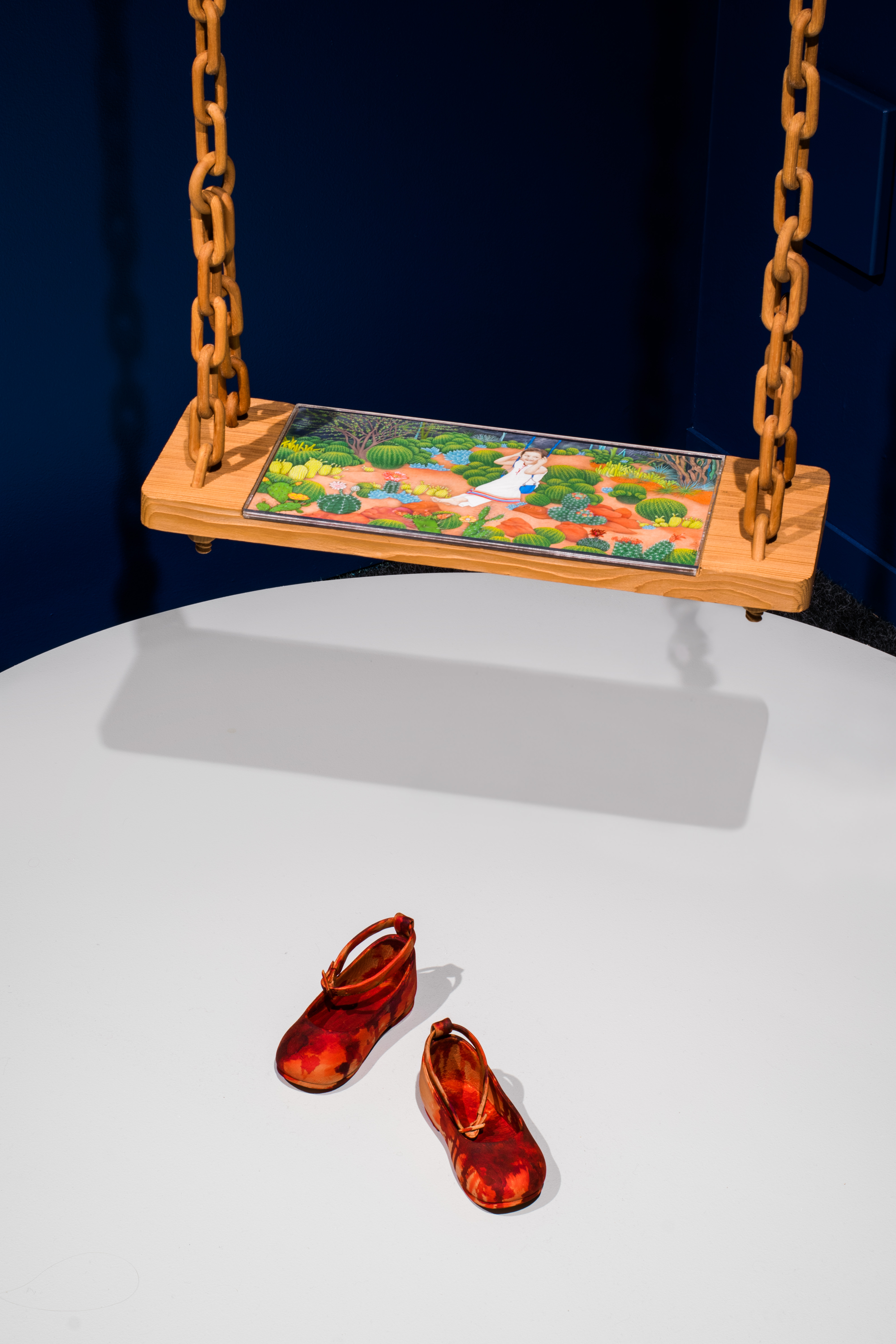 Title: The World is Beautiful, and Dangerous Too Medium:  Swing: Pine wood, carved;  Shoes: Pine wood, carved; red wood stain Installation: 120 x 36 x 36 inches year: 2017 Photo credits: Emilie Smith